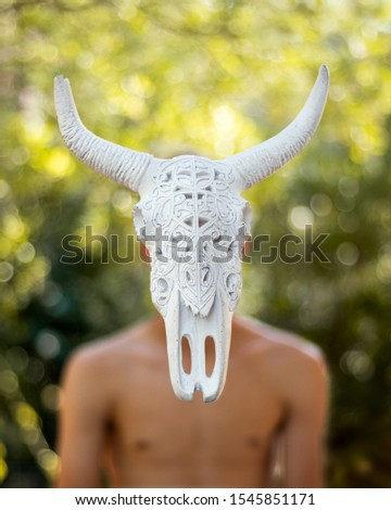 Detailed decorative buffalo dead head hiding a human face. Can illustrate animal cruelty and suffering, nature appropriation, disconnection with wildlife concepts. Copy space. #1545851171