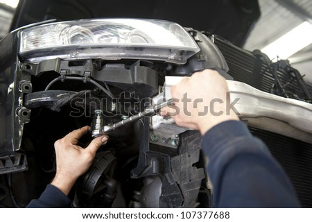 Detailed image of car repair, service and inspection by mechanic in auto garage.