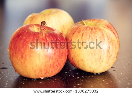 Detailed macrophotography of three yellow-red fresh apples on dark glossy table. Sweet and fresh apples with water drops on dark table with beautiful bokeh background. #1398273032