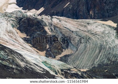 Detailed natural texture of giant mountain covered with snow and ice. Small brooks flow down mountainside. Rock with image of big crying eye. Diagonal snowy line. Fantasy artwork of majestic nature. #1156561984