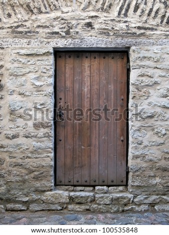 Detailed old antique brown door with metal handle and brick wall around - stock photo