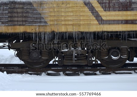 Detailed photo of a frozen car passenger train with icicles and ice on its surface. Railway in the cold winter season #557769466