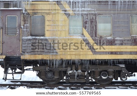 Detailed photo of a frozen car passenger train with icicles and ice on its surface. Railway in the cold winter season #557769565