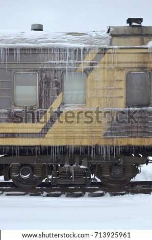 Detailed photo of a frozen car passenger train with icicles and ice on its surface. Railway in the cold winter season #713925961