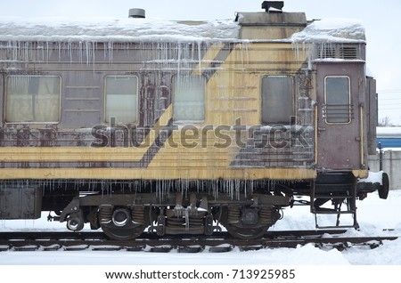 Detailed photo of a frozen car passenger train with icicles and ice on its surface. Railway in the cold winter season #713925985