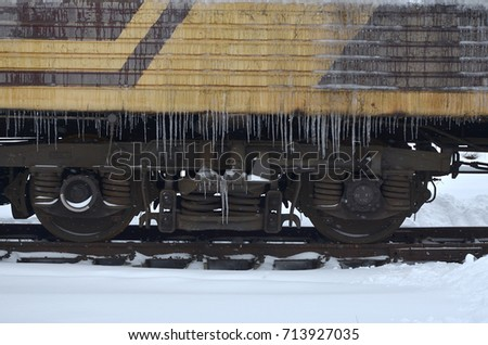 Detailed photo of a frozen car passenger train with icicles and ice on its surface. Railway in the cold winter season #713927035