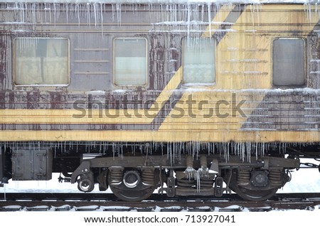 Detailed photo of a frozen car passenger train with icicles and ice on its surface. Railway in the cold winter season #713927041
