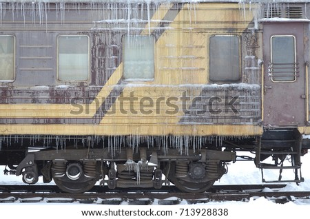 Detailed photo of a frozen car passenger train with icicles and ice on its surface. Railway in the cold winter season #713928838