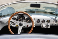 Detailed photo of the interior (dashboard, steering wheel and speedometer) of a classic oldtimer luxury sports car.