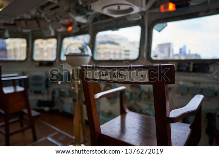Detailed picture on the captain wooden chair with writing captain on bridge of historic warship who served in Royal British navy during World war two and now is exhibited like museum ship in London.