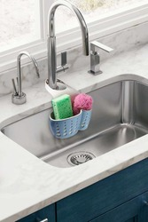 Detailed shot of a blue plastic sponge holder with an adjustable strap. The kitchen organizer with green and pink sponges is hanging on the chrome faucet over the kitchen sink.