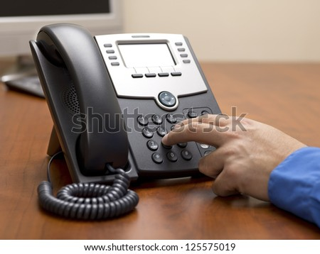Detailed shot of a human hand dialing number on landline phone on office desk.