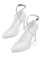 Detailed shot of a pair of transparent shoe straps with steel buckles. The criss-cross shoelaces are fixed on the white leather high-heeled shoes on the white backdrop.