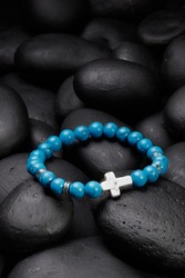 Detailed shot of blue bracelet made of turquoise beads with veins and decorated with silver charms and ivory stone cross. The stylish bracelet is located on black pebble stones.
