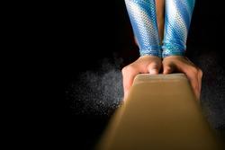 Detailed shot of female gymnast balancing on balance beam with chalk dust on black background.