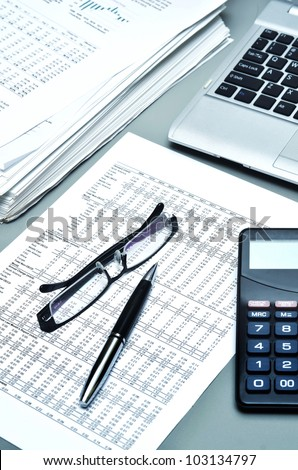 Detailed shot of financial report, ballpoint, glasses, paperwork, laptop and calculator. Can be use as Illustration of financial business, office work, business economy or general business etc.