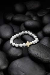 Detailed shot of white bracelet made of beads with gray veins and decorated with silver charms and ivory stone cross. The stylish bracelet is located on black pebble stones.