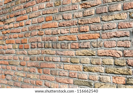 Detailed view at a seamless masonry brick wall of orange colored bricks.