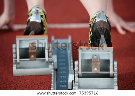 Detailed view of a female sprinter wearing sprinting shoes with spikes, leaving starting blocks