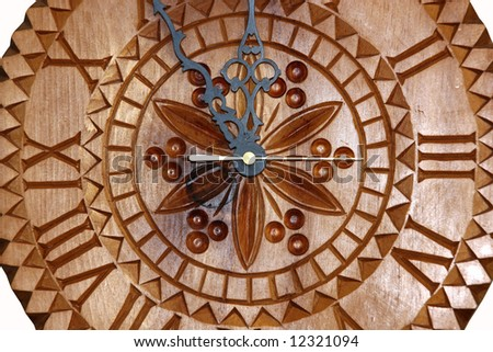 Detailed view of a handmade clock carved on wood showing time five minutes before twelve