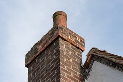 Detailed view of a heavily weathered and cracking brick-built chimney and chimney pot. The pot shows sign of cracking and the brickwork is heavily weathered.