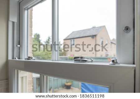Detailed view of a newly installed, energy saving double glazed sash window looking to  small patio area. Сток-фото ©