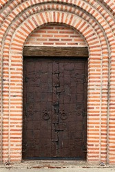 Detailed view of massive metal entrance door of the Church of St. George in Bila Tserkva, Ukraine. Wall with red brick. Typical architecture of kievan rus times.