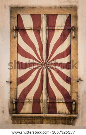 Detailed view of painted window shutter in red and cream colors with yellow casing #1057325159