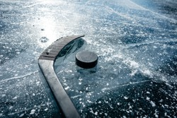 Details close up hockey puck on a frozen pond. Ice skating in nature at sunset in winter. Travel and sports