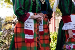 Details of a Bulgarian traditional folklore costume on young women dancers. Elements of a national folk dress with embroidered patterns on girls from the ensemble Trakia. Shot in Plovdiv Bulgaria.