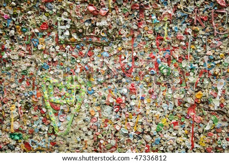Details of a colorful wall covered in bubble gum deposited over the years in the Post Alley section of the Pike Place Market in Seattle show off a gross and disgusting landmark in Seattle.
