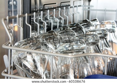 Details of a dishwasher (focus on the front row of glasses)