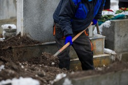 Details of a gravedigger covering a tomb with dirt with a shovel during a burial ceremony on a cold and snowy winter day.