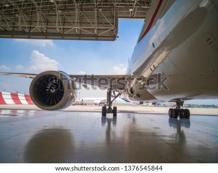 details of a huge passenger plane in maintenance inside a hangar inside an airport #1376545844