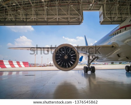 details of a huge passenger plane in maintenance inside a hangar inside an airport #1376545862