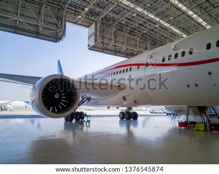 details of a huge passenger plane in maintenance inside a hangar inside an airport #1376545874