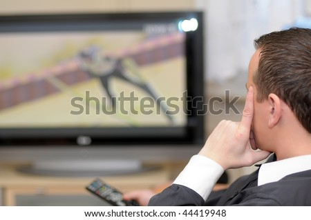 Details of a young man sitting in front of TV and holding a remote control.