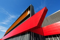 details of aluminum facade with colorful red and orange panels on large shopping mall