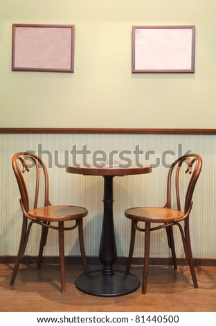 Details of an interior of a small cafe. Just chairs, empty frames and tables.