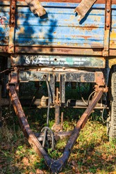 Details of an old and rusty tractor trailer, abandoned trailer of a tractor in a village.