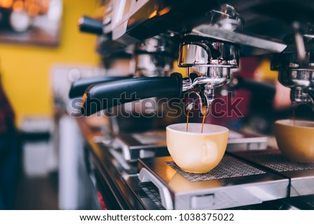 Details of barista preparing fresh espresso on industrial brewing machinery #1038375022