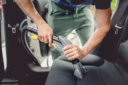 Details of car cleaning - male using professional steam vacuum for dirty car interior