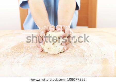 Details of children's hands kneading dough