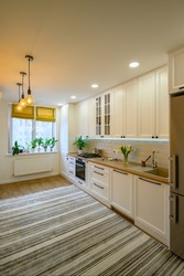 Details of cozy well designed modern kitchen interior with striped carpet and decorative yellow LED bulbs