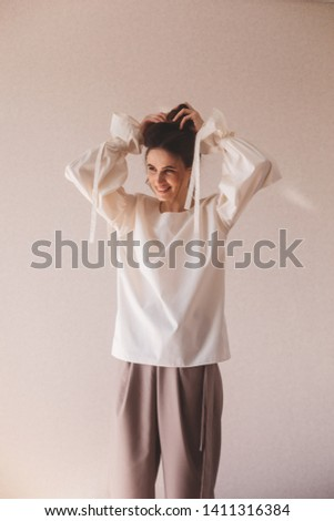 Details of everyday elegant look. Model wearing casual outfit. Milky blouse, beige or brown pantsyin trendy minimalistic style. Brunette with a high bun walking. Woman fixes her high bun.