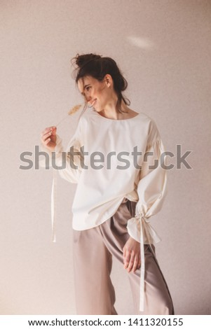Details of everyday elegant look. Model wearing casual outfit. Milky blouse, beige or brown pantsyin trendy minimalistic style. Brunette with a high bun walking. Happy woman enjoying.