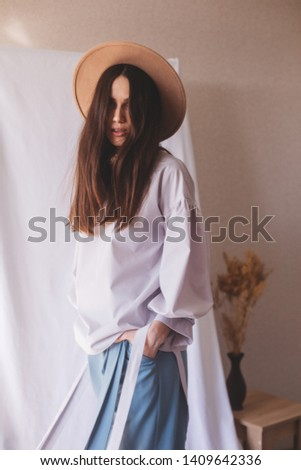 Details of everyday elegant look. Unrecognizable model wearing casual outfit. White blouse, blue pants in trendy minimalistic style. Street fashion. Tape on sleeves. Brunette flying hair woman.