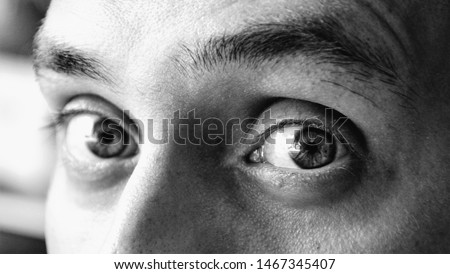 Details of eyes of a handsome man looking at camera. Details of a male face, closeup. Black and white photo. He looks a little bit scared and surprised. Human emotions concept