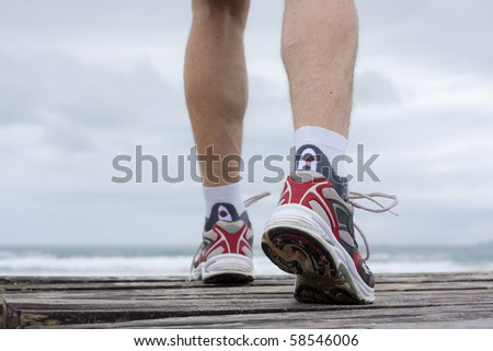 Details of feet of runner in front of a beach