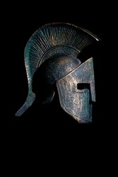 Details of history: Profile of ancient Spartan helmet (replica) isolated on black background, vertical composition